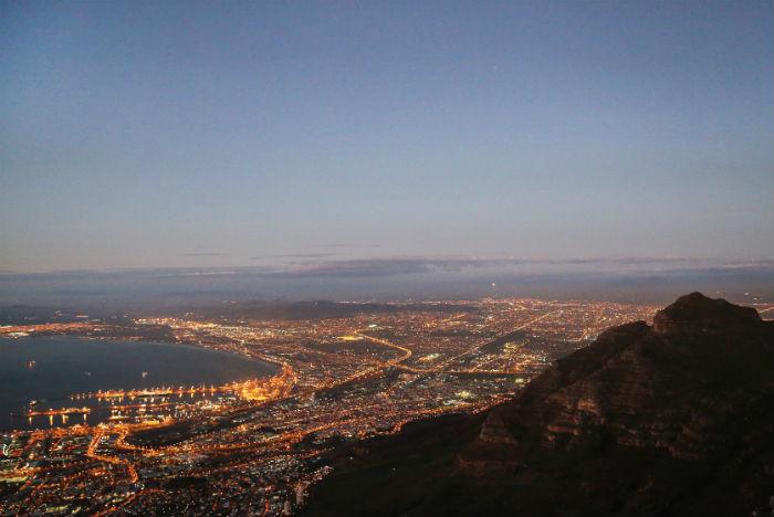 Luzes da cidade são espetáculo à parte quando o sol se põe por trás da Table Mountain