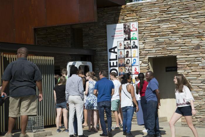Na bilheteria do Museu do Apartheid, visitante recebe ingresso aleatório indicando entrada conforme a cor de pele descrita